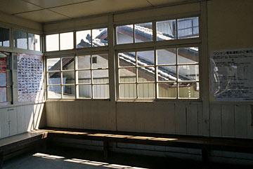 上信電鉄・上州七日市駅の待合室、窓の外眼前には家屋