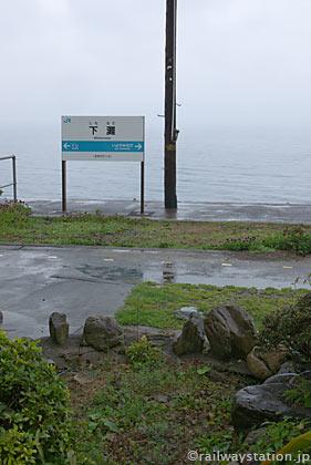 海を背景にした下灘駅プラットホームと駅名標、そいて枯池…