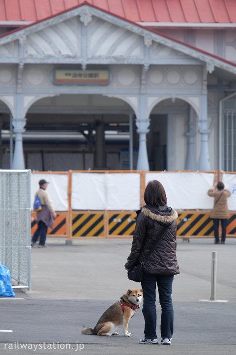 閉鎖された浜寺公園駅旧駅舎を見る犬の散歩中の人とわんこ